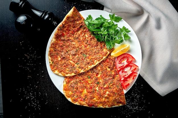 Lahmacun é um prato turco popular. tortilla crocante fina com cordeiro picado, tomate e pimentão na mesa preta