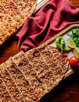 Lahmacun turco de fast-food servido com limão e legumes.