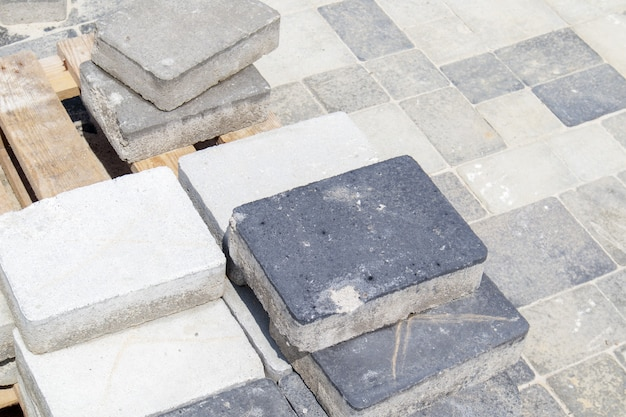 Lajes de pavimentação de concreto ou cinza pavimentadas ou pedras no chão ou na passarela empilhadas em um palete. lajes de pavimentação de concreto no quintal ou pavimentação de estradas. caminho de tijolos do jardim no pátio sobre uma base arenosa.