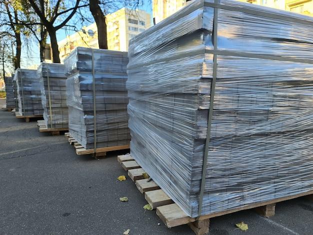 Lajes de pavimentação em filme plástico sobre paletes de madeira na rua