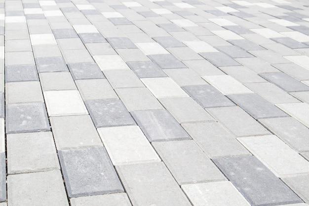 Lajes ou pedras de pavimentação cinza de concreto ou pavimentadas recentemente colocadas para pisos ou passagens. lajes de pavimentação de concreto no quintal ou pavimentação de estradas. caminho de tijolos do jardim no pátio sobre uma base arenosa.