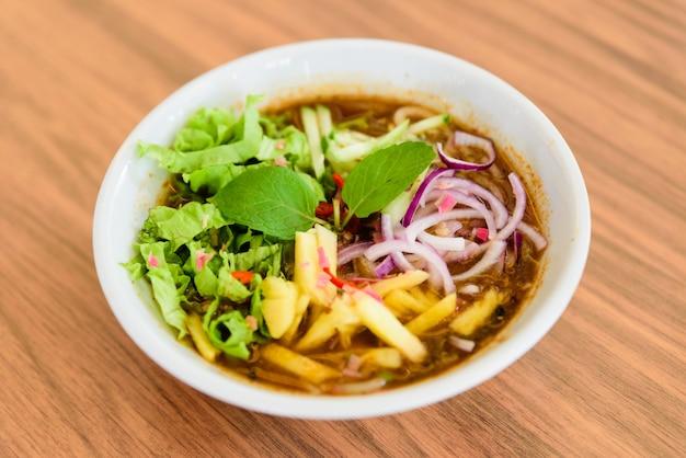 Laksa é uma sopa de macarrão picante popular na malásia na mesa de madeira.