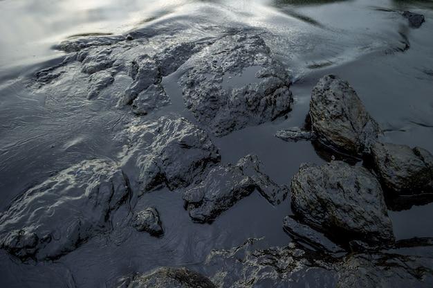 Lama de petróleo que contamina o mar durante o desastre do derramamento de óleo na ilha de samet, rayong, tailândia.