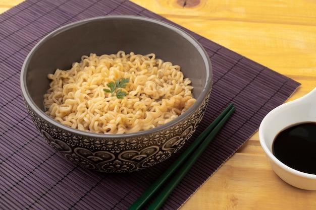 Lamen em uma tigela com hashi e molho de soja.