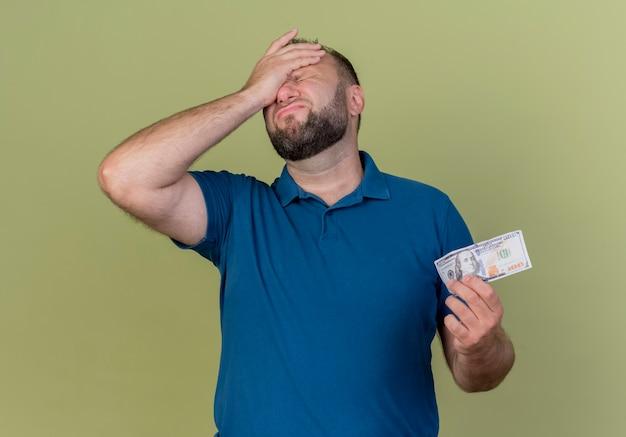 Lamentando o homem eslavo adulto segurando dinheiro e colocando a mão na testa com os olhos fechados