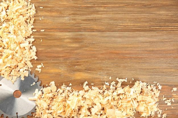 Lâmina de serra circular e aparas de madeira na mesa do carpinteiro
