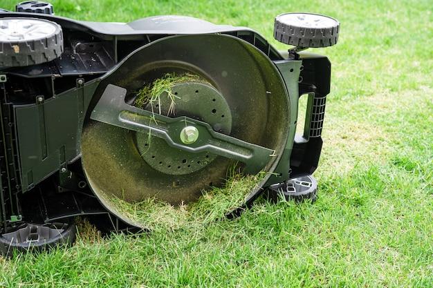 Lâmina na máquina cortador de grama corta grama verde, hobby plantando jardim doméstico.