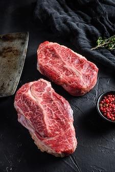 Lâmina superior crua corta carne orgânica ner faca inteligente de carne de açougueiro para churrasco ou grelha vista superior sobre fundo de pedra preta close-up foco seletivo de vista lateral.