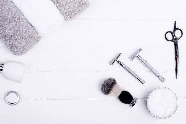 Lâminas, pincel, bálsamo, perfume, toalhas e tesouras em um fundo de madeira.