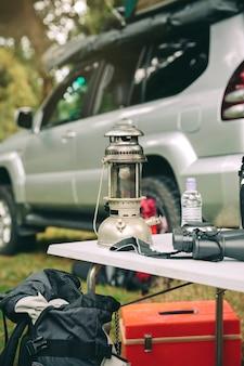 Lâmpada a óleo e binóculos sobre uma mesa de camping na floresta com um veículo offroad ao fundo