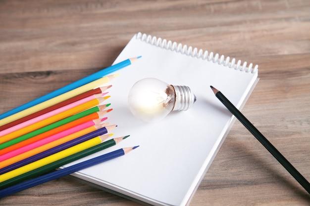 Lâmpada, bloco de notas e lápis coloridos no fundo de madeira.