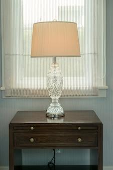 Lâmpada branca na mesa de cabeceira de madeira no quarto de luxo