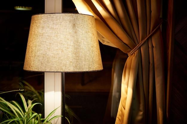 Lâmpada clássica com luz fraca perto da janela.