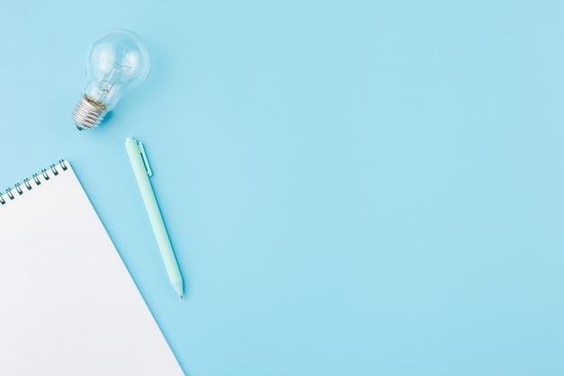 Lâmpada com bloco de notas e uma caneta sobre fundo azul