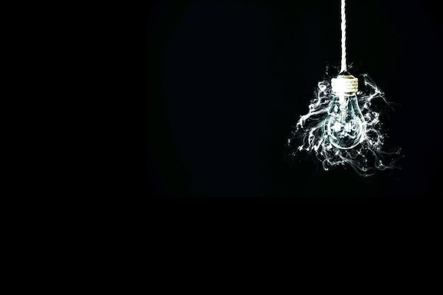 Lâmpada com fumaça pendurada na corda. novo conceito de ideia. isolado em um fundo preto.