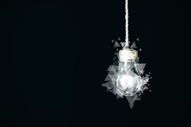 Lâmpada com triângulos pendurados na corda. novo conceito de ideia. idéia de arte. isolado em um fundo preto.