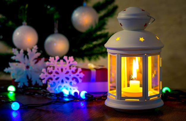 Lâmpada com vela e flocos de neve decorativos perto da árvore de natal_