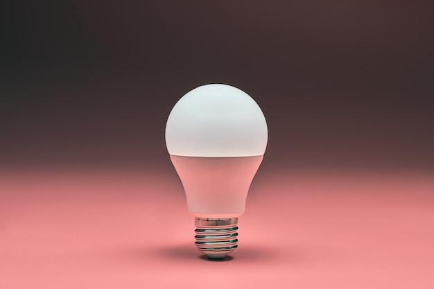 Lâmpada, copie o espaço. conceito de ideia mínima de economia de energia. fundo rosa.