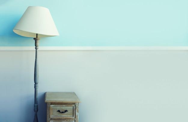 Lâmpada da tocha do assoalho, nightstand de madeira, cortinas no fundo azul pastel da parede.