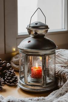 Lâmpada de ângulo alto com vela, pinhas e cobertor