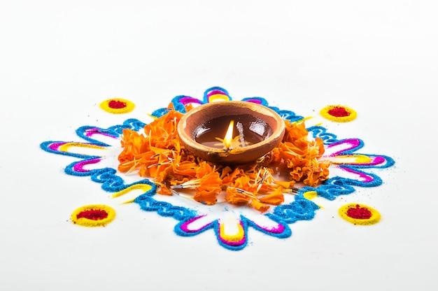 Lâmpada de argila diya acesa durante o festival de diwali. clay diya em rangoli. o festival de luzes hindu indiano chamado diwali.