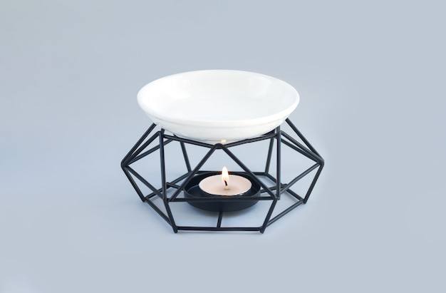 Lâmpada de aroma ou queimador de óleo com vela acesa e óleos essenciais
