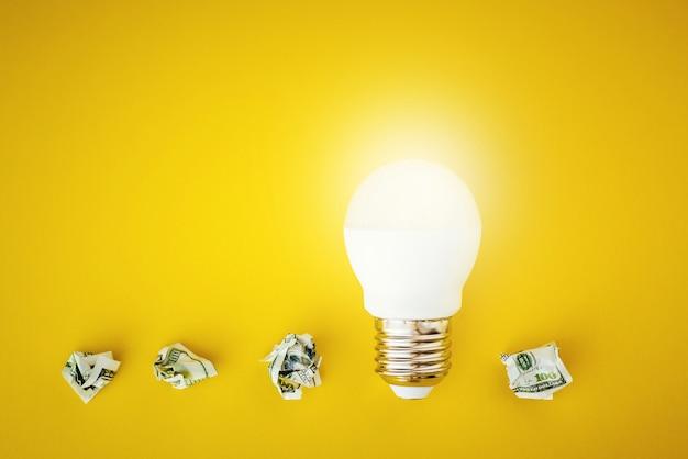 Lâmpada de brilho e notas de dólar de papel amassado em fundo amarelo