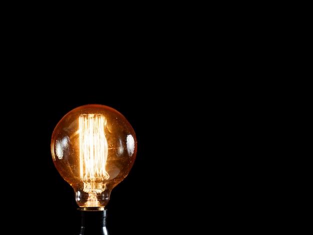 Lâmpada de edison vintage na escuridão. conceito de idéia criativa.