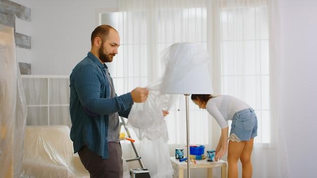 Lâmpada de embrulho de homem com folha de plástico antes de renovar a sala de estar. apartamento de redecoração do casal. construção, reparo, reforma da casa, pintura.