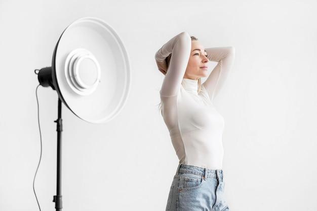 Lâmpada de estúdio e mulher segurando sua cabeça
