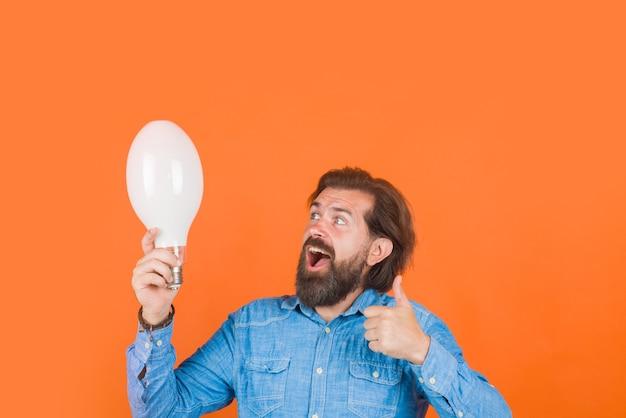 Lâmpada de ideia boa na mão homem feliz com lâmpada grande pensamentos ideia conceito homem barbudo segura luz