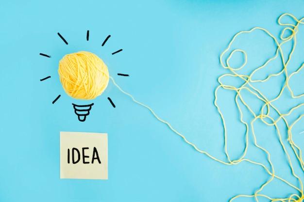 Lâmpada de ideia de lã amarela sobre fundo azul com texto de ideia na nota auto-adesiva