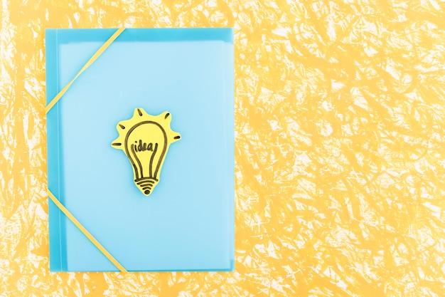 Lâmpada de ideia desenhada no livro de capa azul sobre o pano de fundo padrão