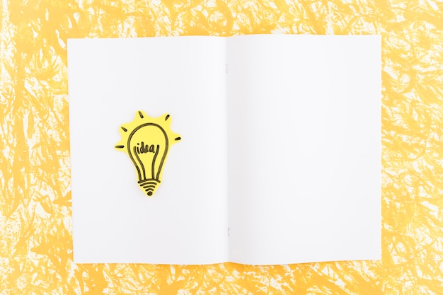 Lâmpada de ideia iluminada desenhada na página em branco sobre o fundo amarelo