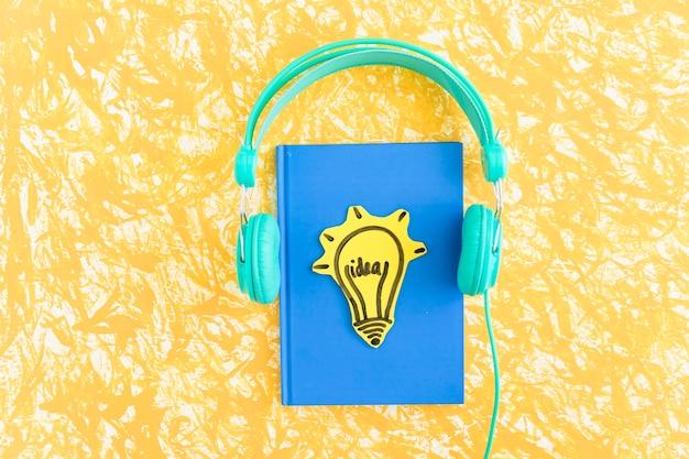 Lâmpada de ideia no caderno de capa azul com fone de ouvido no pano de fundo amarelo