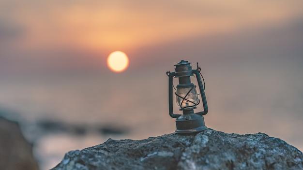 Lâmpada de lanterna na pedra do mar ao amanhecer