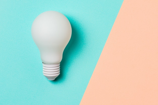 Lâmpada de luz branca em fundo azul e rosa