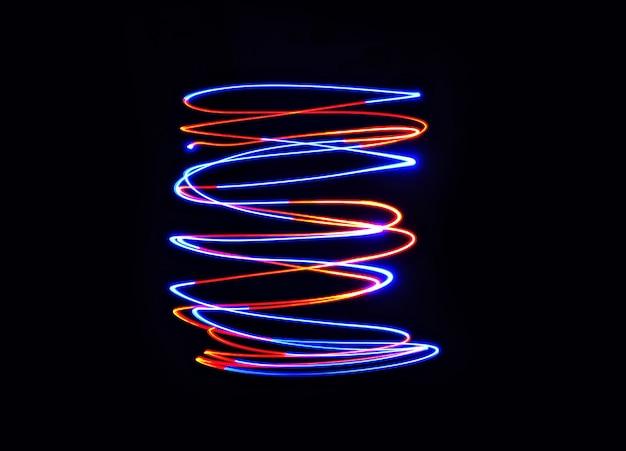 Lâmpada de luz colorida movimenta a torção em fotos de longa exposição no escuro.