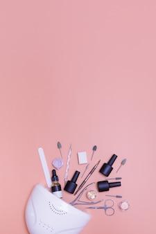 Lâmpada de manicure e ferramentas para aplicar a vista superior de verniz em um fundo colorido. foto do conceito de manicure do salão de beleza