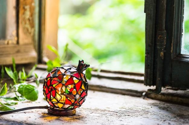 Lâmpada de mosaico na janela