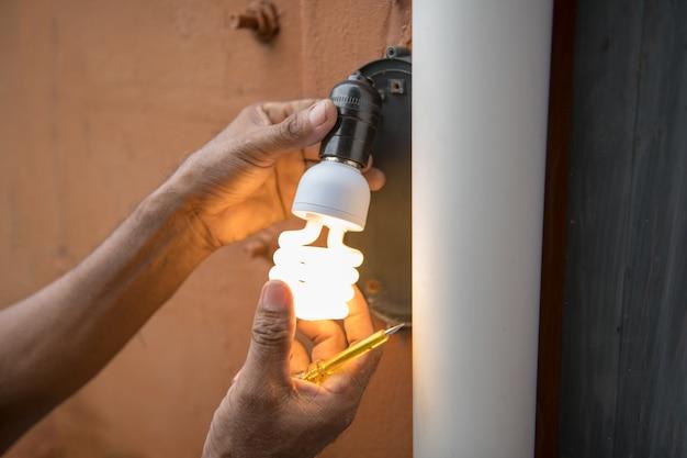 Lâmpada de mudança de eletricista na lâmpada de parede exterior de casa