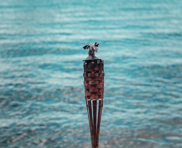 Lâmpada de óleo de bambu de tikki em uma praia