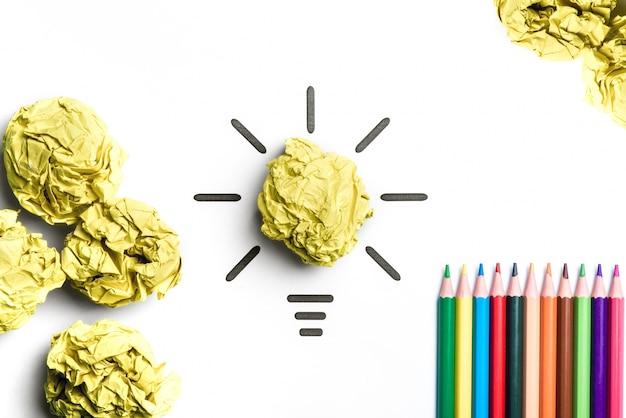 Lâmpada de papel amassado e lápis de cor. metáfora para boa ideia. conceito de inspiração