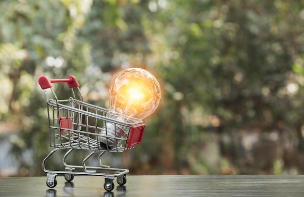 Lâmpada de poupança de energia com carrinho de compras financeira e conceito de compras