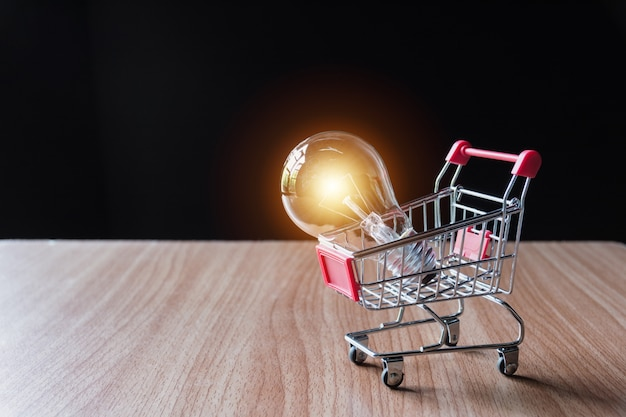 Lâmpada de poupança de energia com pilhas de moedas e carrinho de compras para salvar