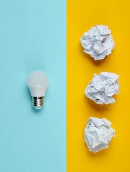 Lâmpada de poupança de energia e bolas de papel amassado na mesa azul amarela. conceito de negócio minimalista, idéia. vista do topo