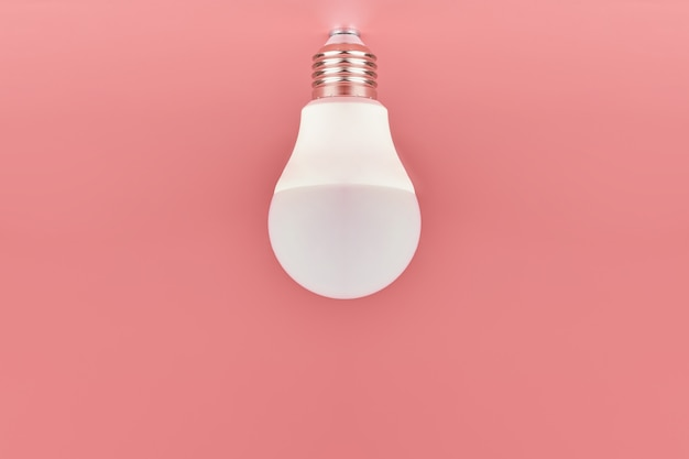 Lâmpada de poupança de energia em fundo rosa