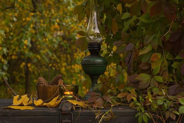 Lâmpada de querosene velha em uma superfície de madeira velha no jardim do outono