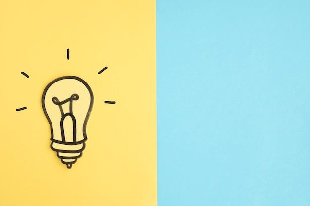 Lâmpada de recorte de papel em fundo amarelo e azul