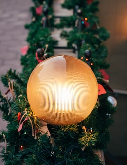 Lâmpada de rua redonda brilhando entre as decorações de natal